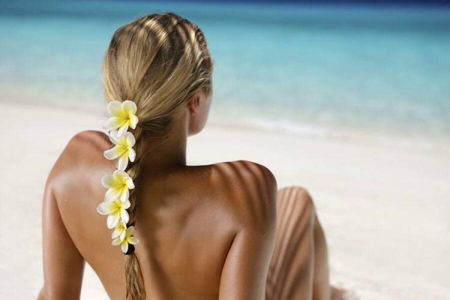 une femme en train de bronzer avec des fleurs dans les cheveux