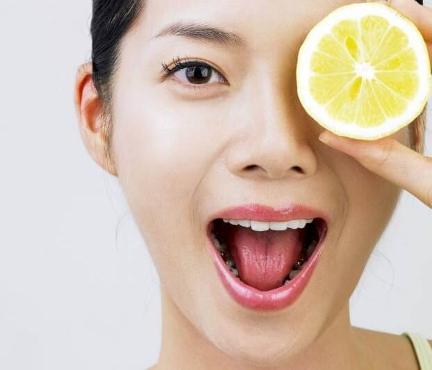 une femme avec une rondelle de citron sur l'oeil